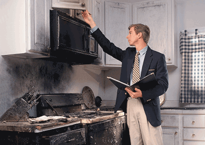 Insurance agent inspecting fire damage on stove, countertop, and shelf