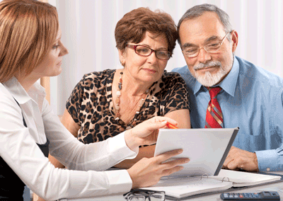 An elderly couple being presented some investment options by a financial counselor