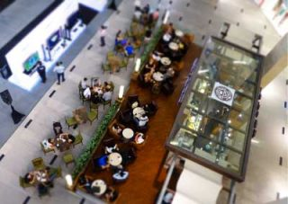 Busy building lobby containing a coffee shop and a wide-screen television showcase seen from above