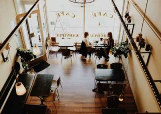 Café interior seen from the roof near the till pointing at the front window where there are two women discussing something over coffee