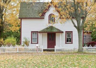 Small 2-story Italiante Centered gable cottage with white facade and red trim. It has columns beside the doors.