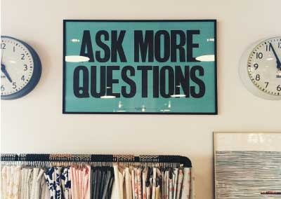 "Wall with a poster between two clocks and above a clothes rack. The poster sas ""Ask More Questions"""