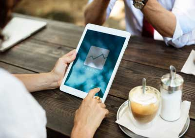 Person using an ipad and turning on a financial planning application over a wooden table with other person facing them. Focus is on the ipad and facing down so no faces are in the frame.