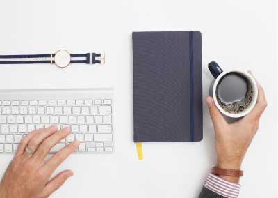 Person's hands, one is over a keyboard, one is holding a mug of coffee. There is also a notebook and a watch on the desk.