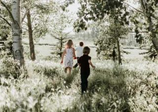 A girl dressed in white and two boys, one dressed in white and one in black walking out of a forest into a clearing