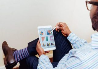 Man in striped suit looking down at ipad with financial data graphs displayed
