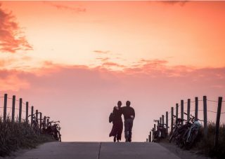 A man and woman walking down a sunset road with an arm around one another