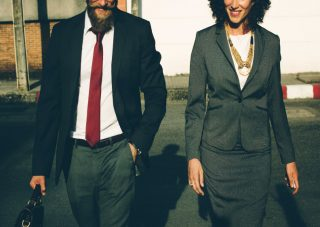 Man and woman in business outfits walking and having a discussion
