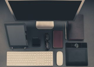 An array of business devices (tablet, phone, glasses, planner, notebook, keyboard, mouse, trackpad, and computer screen) arranged on a desk