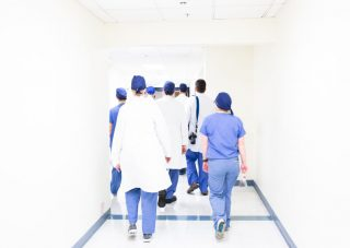 A group of doctors and nurses in scrubs walking down a hospital hallway