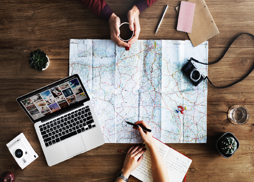 Two people meeting and planning a trip using a pen, journal, and a map