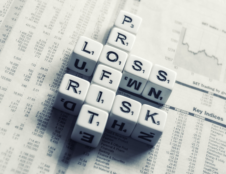 """Lettered dice set in a crossword fashion and spelling the words """"profit"""", """"loss"""", and """"risk"""""""
