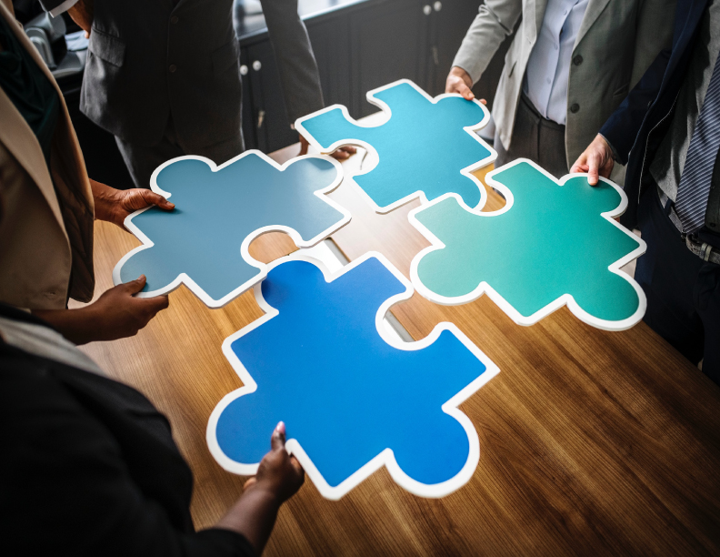 Large puzzle pieces being put together on a boardroom table