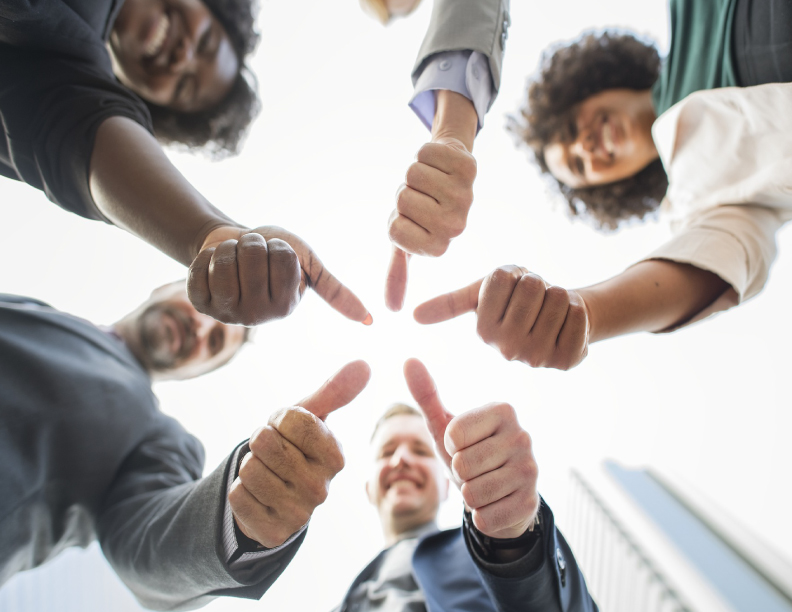 A group of people in a circle with hands extended giving a thumbs up gesture