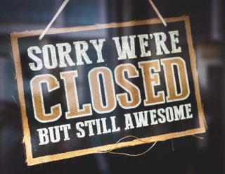 A sign hanging in a window and reading 'Sorry, we're Closed, but still awesome'