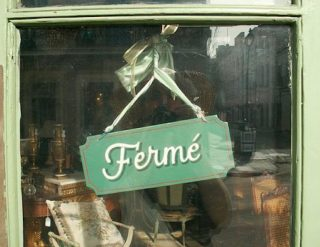 "sign in an antique shop window labeled ""closed"" in French"