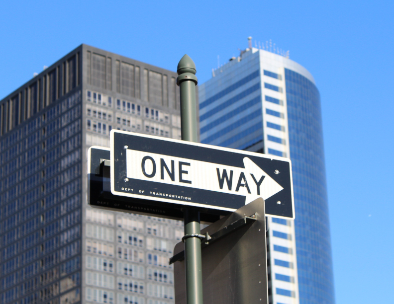 A one way street sign with skyscrapers in the background.