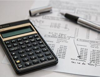A calculator and pen resting on a financial document