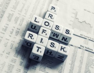 Lettered dice set in a crossword fashion and spelling the words: profit, loss, and risk