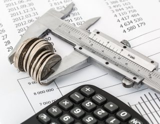 A small stack of coins being measured in a vernier caliper, laying on a financial document