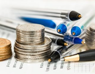 Closeup of a few small stacks of coins next to several ballpoint pens
