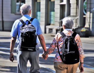 Two seniors are travelling with their backpacks.