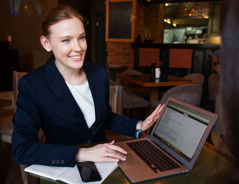 A professional-looking lady is holding a laptop with smile on her face.
