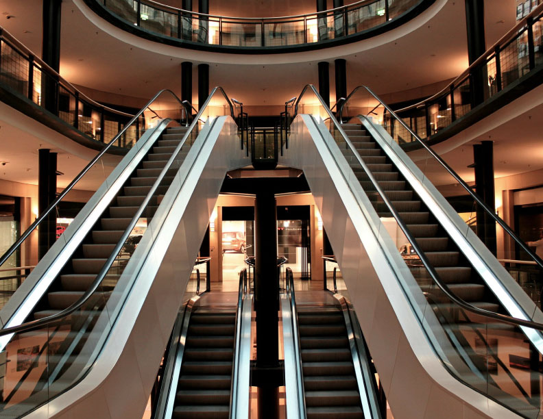 The inside of a shopping mall with escalators.
