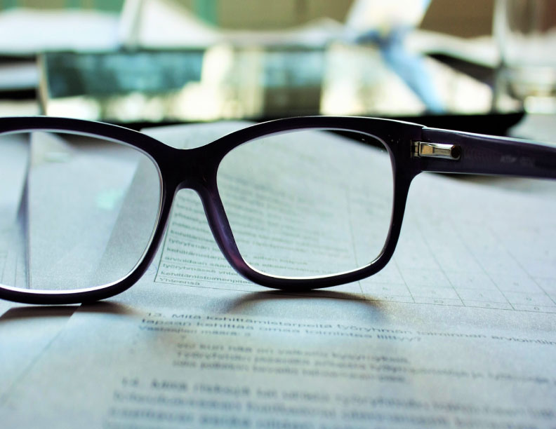 A pair of glasses sitting on some paper.