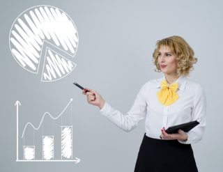 A woman pointing out a graph and a chart.